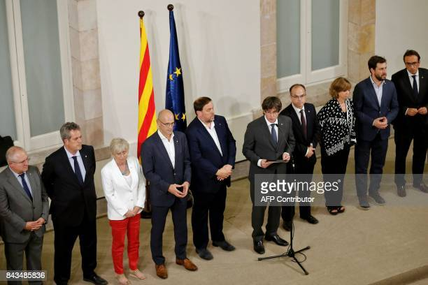 President of the Catalan Government Carles Puigdemont , standing in front of Catalan government's members makes an institutional declaration after...