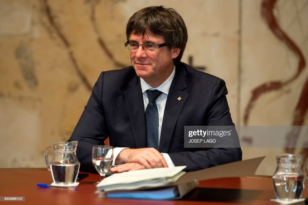 President of the Catalonian regional government, Carles Puigdemont smiles as he attends a regional government meeting on September 26, 2017 at the Generalitat Palace in Barcelona. Spain's chief public prosecutor refused on September 25, 2017 to rule out the arrest of Catalan president Carles Puigdemont for pushing ahead with an independence referendum deemed illegal by Madrid. / AFP PHOTO / Josep LAGO