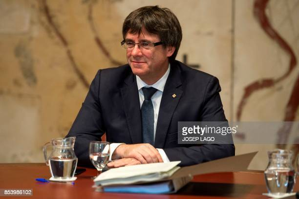 President of the Catalonian regional government Carles Puigdemont smiles as he attends a regional government meeting on September 26 2017 at the...