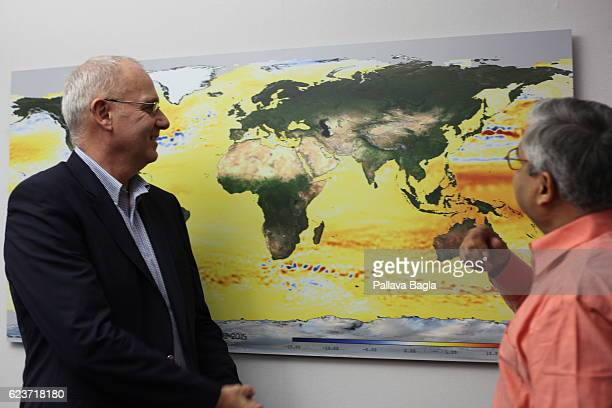 President of the Centre National d'Etudes Spatiales JeanYves Le Gall demonstrates a map of the world that shows how the sea levels are rising on...