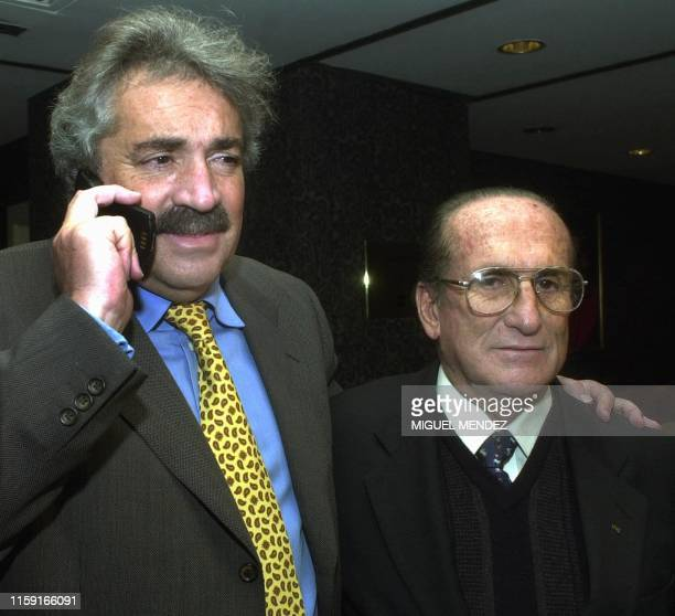 President of the Colombian Soccer Federation Alvaro Fina talks on a cellular phone while he poses for photographers with the vice president of this...