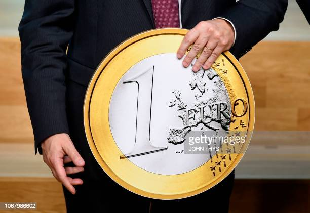 President of the ECB Mario Draghi poses with a replica of an EU coin marking the twentieth anniversary of the Euro during an Eurogroup meeting at the...
