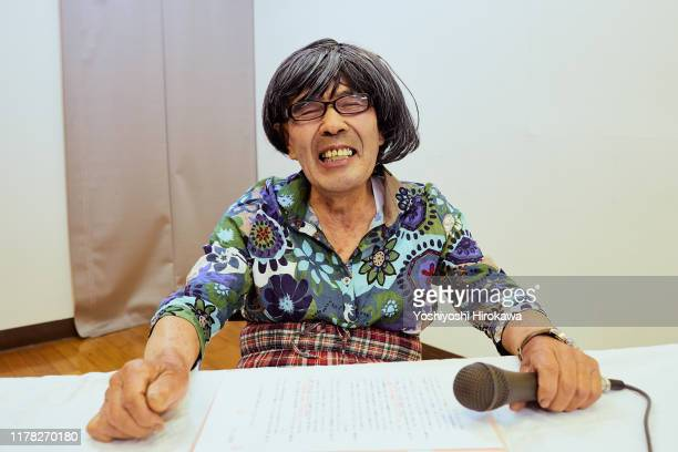 president of the elders association wearing a wig and women's clothes for entertainment at a longevity event - chairperson stock pictures, royalty-free photos & images