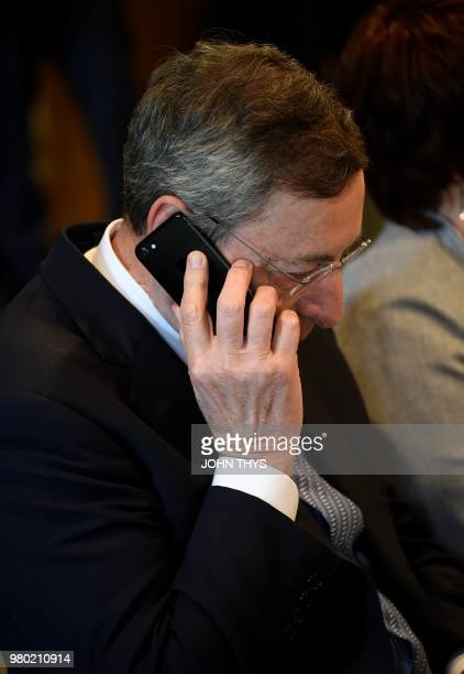President of the European Central Bank Mario Draghi talks on the phone during the 20th anniversary Eurogroup meeting at the Senningen castle in...
