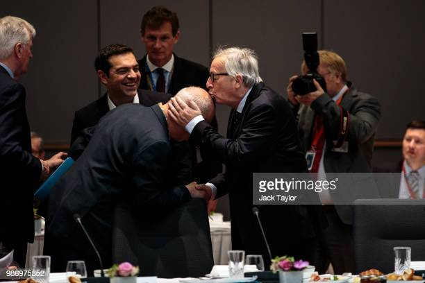 President of the European Commission JeanClaude Juncker kisses a man's head as Prime Minister of Greece Alexis Tsipras looks on ahead of roundtable...