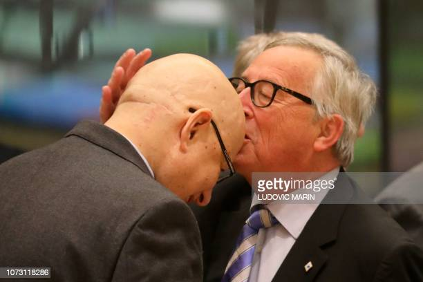 TOPSHOT President of the European Commission JeanClaude Juncker kisses an attendee on his head as he arrives on December 14 2018 in Brussels during...