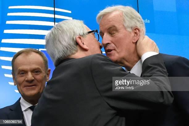 President of the European Commission JeanClaude Juncker kisses EU chief Brexit negotiator Michel Barnier next to European Council President Donald...