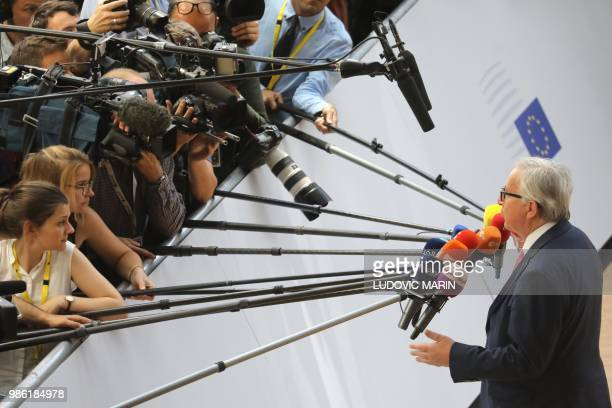 President of the European Commission JeanClaude Juncker speaks to journalists as he arrives to take part in an European Union leaders' summit focused...