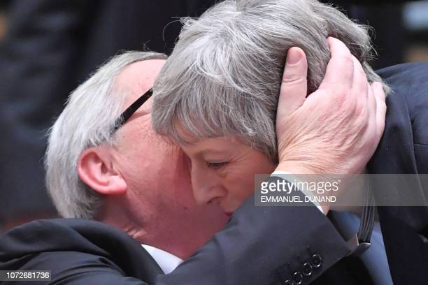 President of the European Commission JeanClaude Juncker whispers in the ear of Britain's Prime Minister Theresa May as she arrives to attend a...