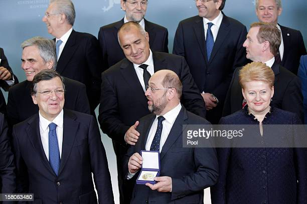 President of the European Parliament Martin Schulz holds the medal of the Nobel Peace Prize as he poses with President of the European Commission...