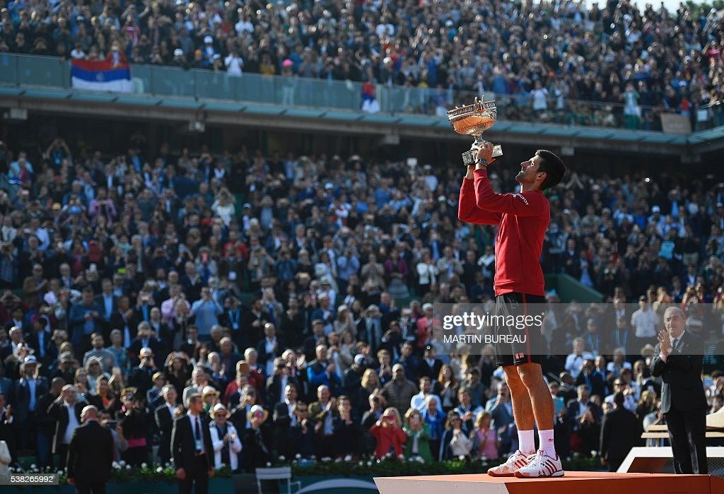 President of the Federation Francaise de Tennis Jean Gachassin (R) looks on as Serbia's Novak Djokovic holds up his trophy after winning the men's final match against Britain's Andy Murray at the Roland Garros 2016 French Tennis Open in Paris on June 5, 2016. / AFP / MARTIN