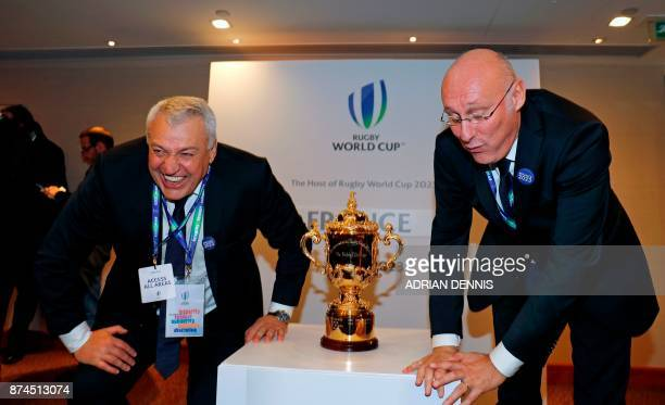 President of the French bid Claude Atcher and French rugby President Bernard Laporte react as they attempt to stand up after crouching for a...