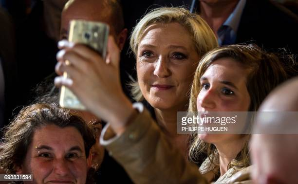 President of the French farright Front National party Marine Le Pen poses for a selfie photo during a campaign rally on June 8 2017 in Calais in...