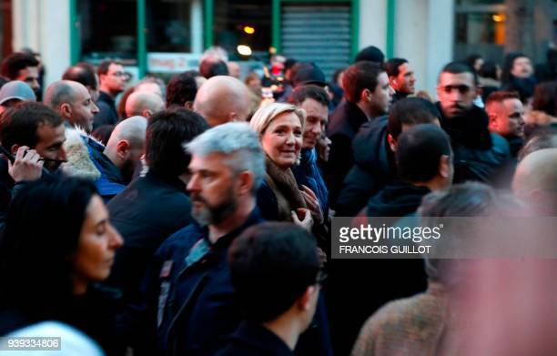 President of the French farright Front National party Marine Le Pen walks with others in Paris on March 28 during a silent march in memory of...