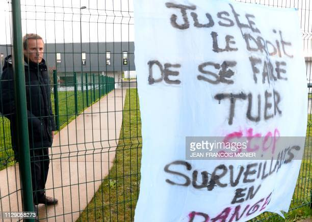 President of the French rightwing Debout la France party Nicolas DupontAignan stands behind a banner reading 'Just the right to get killed stop...