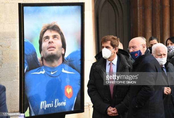 President of the French Rugby Federation Bernard Laporte and Stade Francais' former president Max Guazzini stand next to a photograph of Christophe...