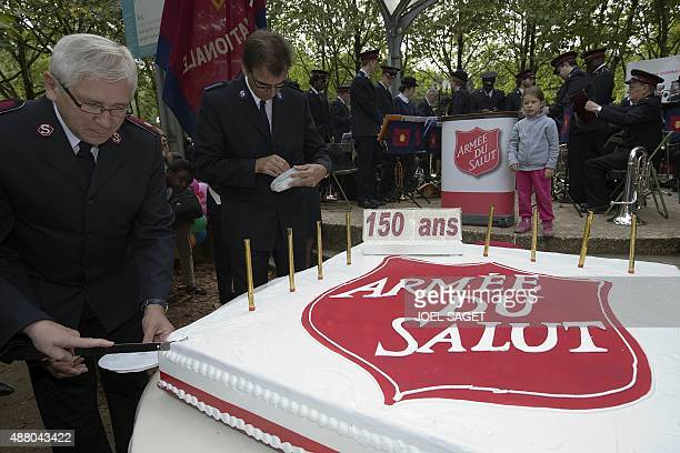 President of the French Salvation Army Daniel Naud cuts a cake picturing the Salvation Army's logo on September 13 2015 during a ceremony in Paris to...