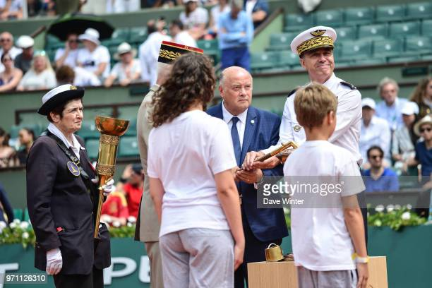 President of the French Tennis Federation Bernard Giudicelli supervises the arrival of the flame lit from the eternal flame at the tomb of the...