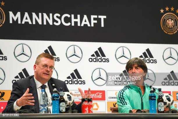President of the German Football Association Reinhard Grindel flanked by Germany's coach Joachim Loew gestures as he speaks during a press conference...