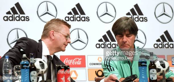 President of the German Football Association Reinhard Grindel speaks with Germany's coach Joachim Loew during a press conference in Vatutinki near...