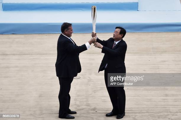 President of the Greek Olympic Committee Spyros Kapralos hands over the flame to President and CEO of the Pyeongchang Organizing Committee for the...