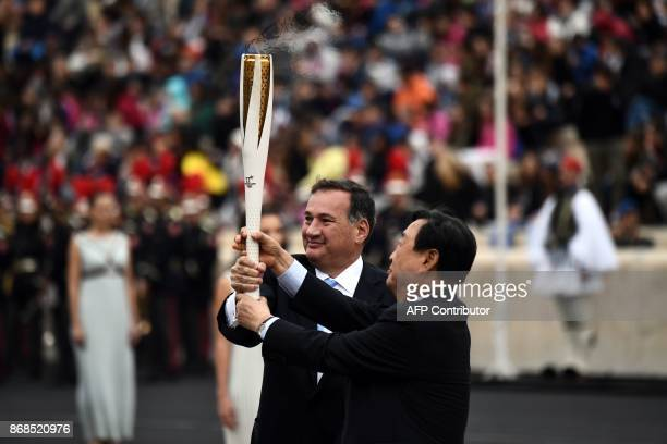 President of the Greek Olympic Committee Spyros Kapralos hands The Olympic Flame over to President and CEO of the Pyeongchang Organizing Committee...
