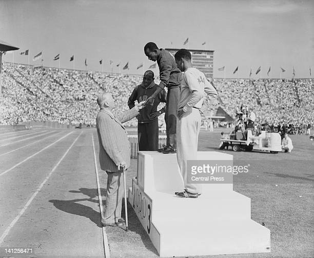 President of the International Olympic Committee Sigfrid Edstrom presents the gold medal for the Men's 100 metres event to Harrison Dillard of the...