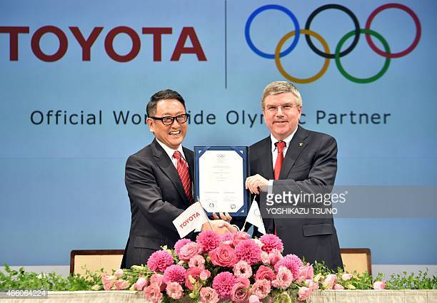 President of the International Olympic Committee Thomas Bach and Japanese auto giant Toyota Motor president Akio Toyoda display their agreement of...