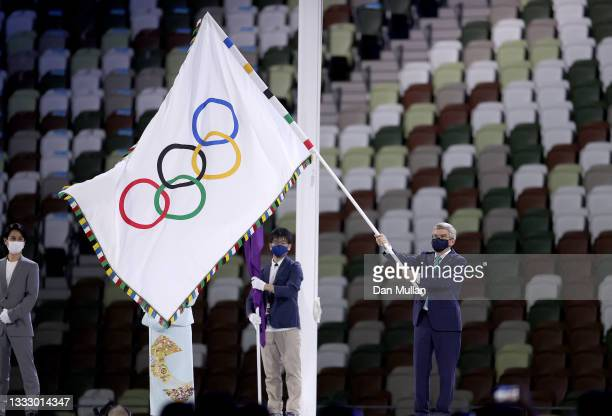 President of the International Olympic Committee, Thomas Bach prepares to handover the Olympic flag during the Closing Ceremony of the Tokyo 2020...