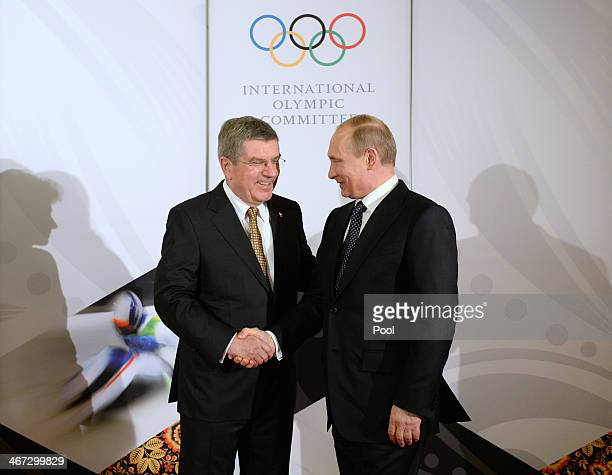 President of the International Olympic Committee Thomas Bach shakes hands with Russian President Vladimir Putin before the IOC Gala Dinner on the eve...