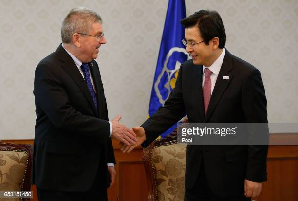 President of the International Olympic Committee Thomas Bach shakes hands with South Korea's Prime Minister and acting President Hwang Kyoahn on...