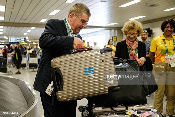 President of the International Olympic Committee Tomas Bach and his wife Claudia carry their bags on their arrival for Rio 2016 Olympic games at...