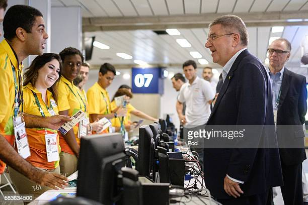 President of the International Olympic Committee Tomas Bach asks a volunteer for his credential card on his arrival for Rio 2016 Olympic Games at...