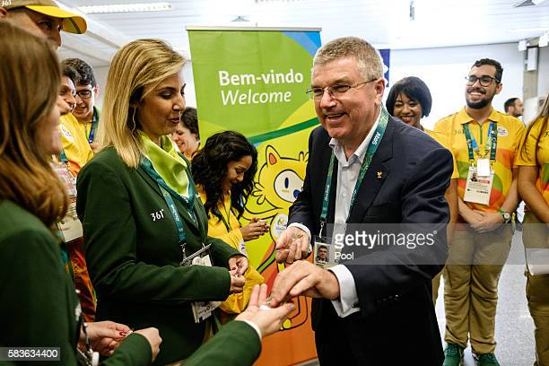 President of the International Olympic Committee Tomas Bach delivers Olympic pin badges on his arrival for Rio 2016 Olympic games at Antonio Carlos...