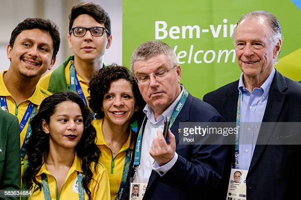 President of the International Olympic Committee Tomas Bach looks at a 360degree camera given by an official videographer as Carlos Nuzman President...