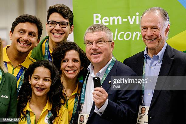 President of the International Olympic Committee Tomas Bach takes pictures with a 360degree camera given by an official videographer as Carlos Nuzman...