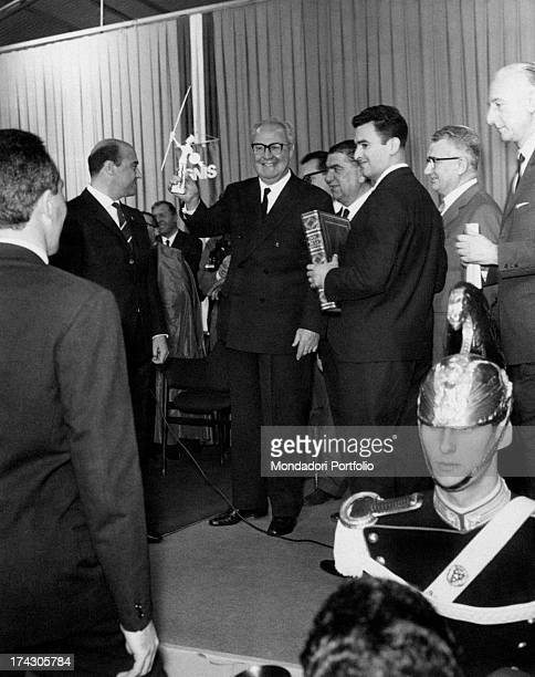 President of the Italian Republic Giuseppe Saragat smiling and raising the symbol of the Ignis household appliances' factory Giuseppe Saragat visited...