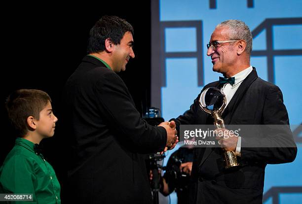 President of the Jury director Luis Minarro from Spain and director George Ovashvili from Georgia shake hands as he receives the Grand Prix Crystal...