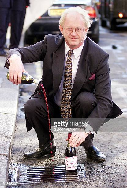President of the National Union of Farmers Ben Gill pours Beaujolais Nouveau down a drain 18 November 1999 outside the Midas Touch bar in Soho in...