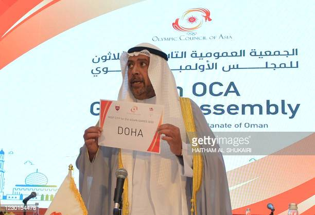 President of the Olympic Council of Asia Ahmad al-Fahad al-Sabah holds a placard announcing Doha as the host of the 21st Asian Games 2030 during the...
