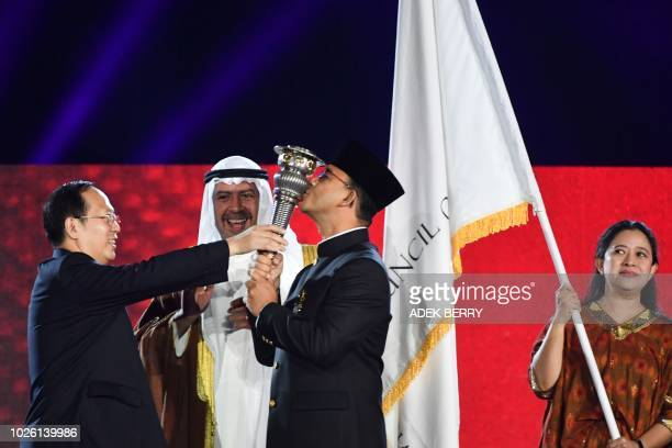 President of the Olympic Council of Asia Sheikh Ahmad alFahad alSabah smiles next to a representative of the Hangzhou Asian Games Organizing...