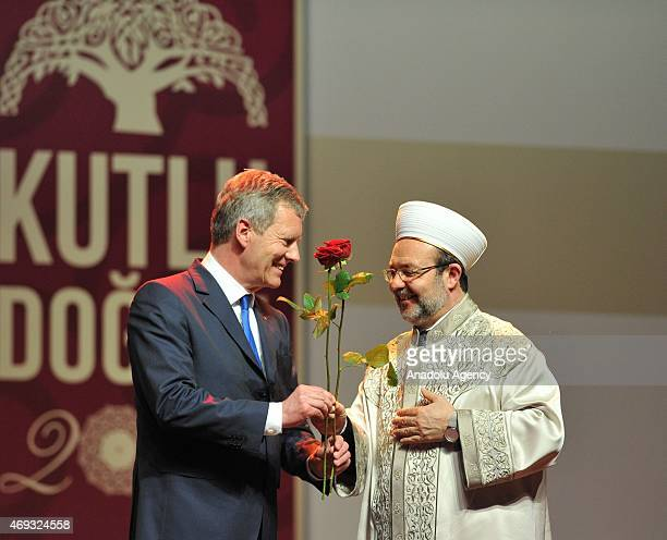 President of the Presidency of Religious Affairs Mehmet Gormez gives a china engraving and red rose to former German president Christian Wulff who...