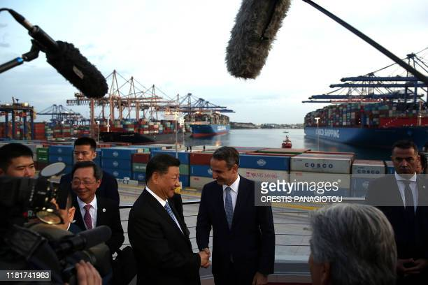 President of the Republic of China Xi Jinping and Greek Prime Minister Kyriakos Mitsotakis shake hands as they visit the cargo terminal of Chinese...