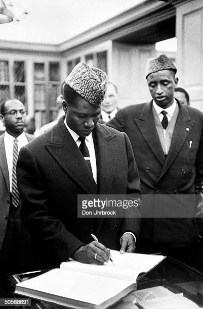 President of the Republic of Guinea Sekou Toure signing a guest book during a visit to the US