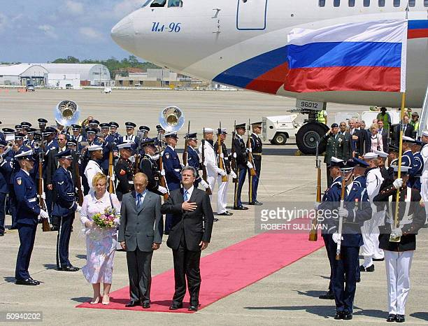 President of the Russian Federation Vladimir Putin and his wife Lyudmila stand with Deputy US Chief of Protocol Jeff Eubank during arrival ceremonies...