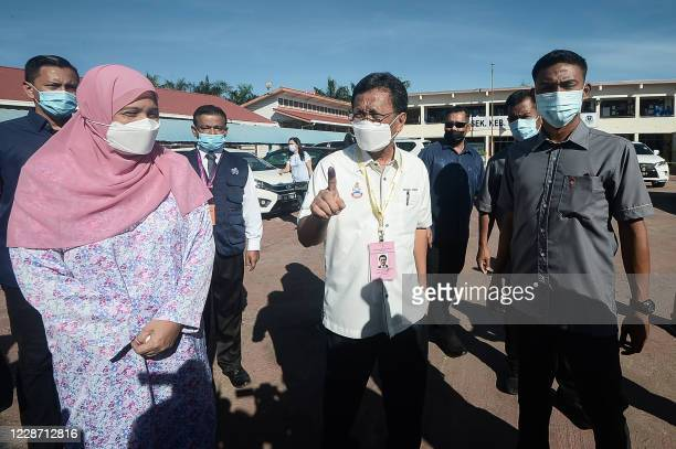 President of the Sabah Heritage Party Shafie Apdal , shows his inked finger after casting his vote at a polling station during state elections in...