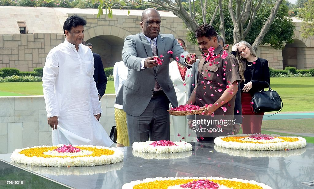 President of the United Nations General Assembly, John W. Ashe of Antigua and Barbuda (C) is watched by officials as he scatters rose petals during a visit to Rajghat, the memorial to Mahatma Gandhi in New Delhi on March 21, 2014. Italy has appealed to the United Nations to help free its two Italian marines who are being tried in India for killing two Indian fishermen in 2012. Ashe is in India for a two-day official visit.