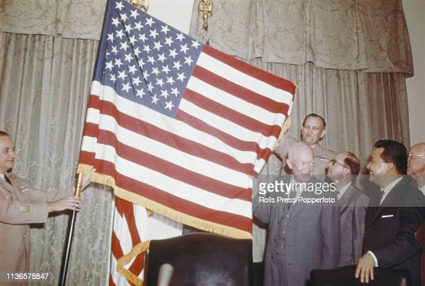 President of the United States, Dwight D. Eisenhower helps to unfurl the new 50-star national flag of the United States after signing a proclamation...