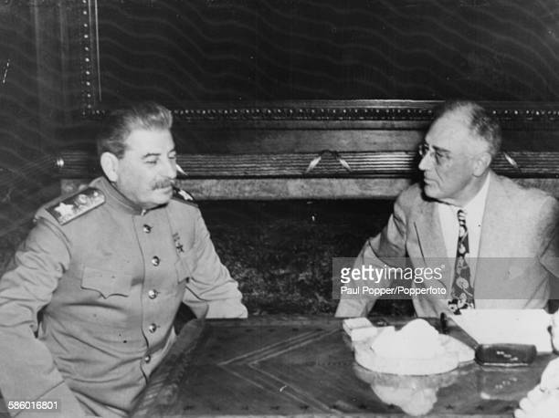 President of the United States Franklin D Roosevelt talks with Soviet leader Joseph Stalin as they sit opposite each other at a table at an Allied...