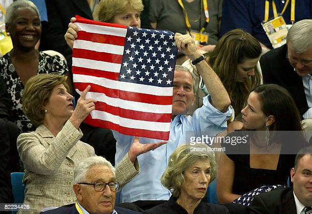 President of the United States George W Bush holds up the American Flag the wrong way before wife Laura Bush instructs him to turn it around at the...